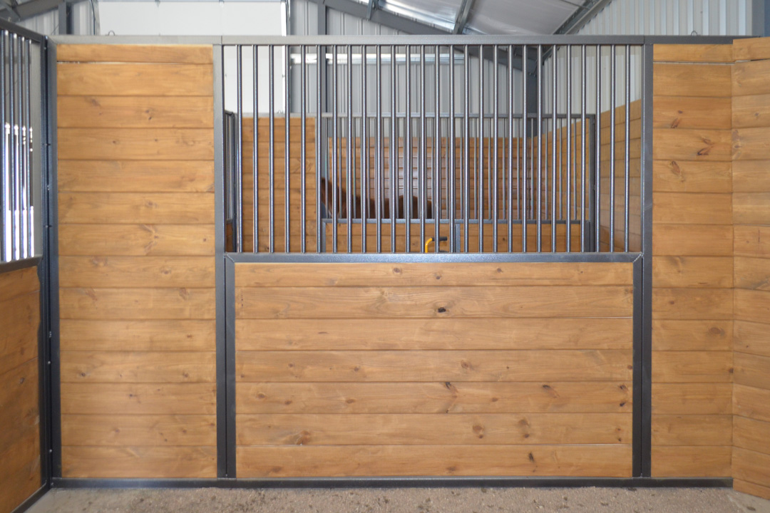 A horse stall divider with light horizontal wood